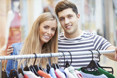 Couple Looking At Clothes On Rail In Shopping Mall Stock Photo