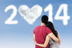 Couple looking at clouds shaped 2014 Royalty Free Stock Photography