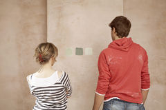 Couple Looking At Color Samples On Wall Stock Photo
