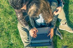 Couple looking at computer in a park royalty free stock photography