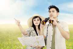 Couple looking for directions on the meadow Royalty Free Stock Photos