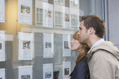 Couple Looking At Display At Real Estate Office Royalty Free Stock Images