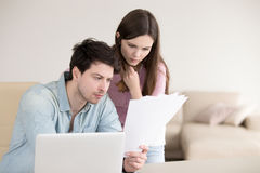 Couple looking at documents, calculating bills, reading letters,. Young serious men holding papers, reading them attentively, sitting with laptop indoors stock photos