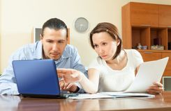 Couple looking  documents in laptop Royalty Free Stock Images