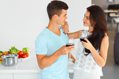 Couple looking at each other, drinking red wine in kitchen. stock photo