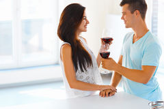 Couple looking at each other, drinking red wine in kitchen. Royalty Free Stock Image