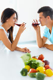 Couple looking at each other while drinking red wine in kitchen Royalty Free Stock Images