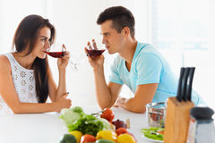 Couple looking at each other while drinking red wine in kitchen Royalty Free Stock Photography