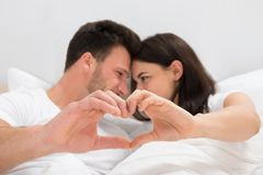 Couple looking at each other forming heart shape Royalty Free Stock Images
