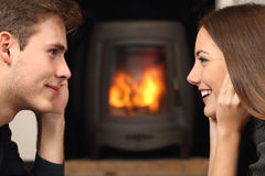 Couple looking each other in front a fireplace. Side view of a couple flirting and looking each other in front a fireplace Stock Photography