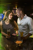 Couple looking at each other while having beer at bar counter Royalty Free Stock Photos