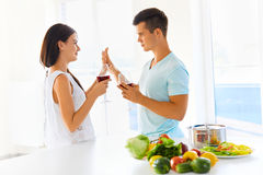 Couple looking at each other, holding glasses of red wine in kit Stock Images