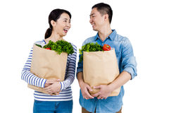 Couple looking at each other while holding grocery bags Royalty Free Stock Photos