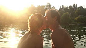 Couple looking at each other and kissing while sitting by the river at sunset stock footage