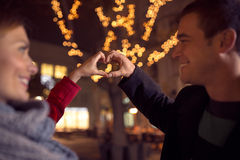 Couple looking at each other and making heart shape Stock Photography