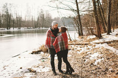 Couple looking each other near winter lake under plaid Royalty Free Stock Photo