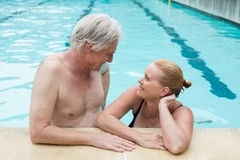 Couple looking at each other at poolside Royalty Free Stock Photos