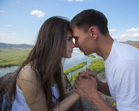 Couple looking into each other's eyes. Happy Young Couple looking into each other's eyes in mountains with river Royalty Free Stock Photos