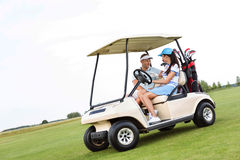 Couple looking at each other while sitting in golf cart against clear sky Royalty Free Stock Images