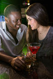 Couple looking at each other and smiling while having drinks Royalty Free Stock Images