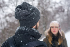 Couple looking at each other while it is snowing Stock Photos