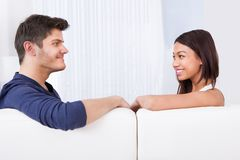 Couple looking at each other on sofa Royalty Free Stock Photos