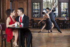 Couple Looking At Each Other While Tango Partners Performing. Loving young couple looking at each other while tango partners performing in cafe Royalty Free Stock Photos