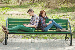 A couple looking each in their mobile phone. A young couple sitting in a park on a bench looking each into their mobile phone and looking away from each other Royalty Free Stock Images