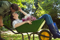 Couple looking face to face while pushing wheelbarrow in garden. On a sunny day Royalty Free Stock Images
