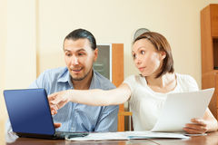 Couple looking financial documents in laptop Stock Photos