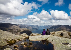 Couple looking at fjord from Kjerag area in Norway stock image