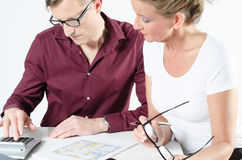 Couple looking at floor plans for new place. Calculating stock photo