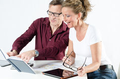 Couple looking at floor plans for new place. And looking into calendar stock image