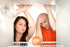 Couple looking in fridge. Young couple looking at ripe apple in otherwise empty refrigerator Stock Image