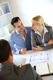 Couple looking at future house plans. Couple meeting real-estate agent to buy property Royalty Free Stock Image
