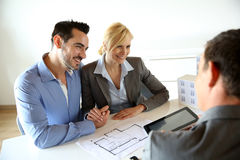 Couple looking at future house plans. Couple meeting real-estate agent to buy property Stock Photo
