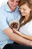 Couple looking at heart-shaped bowl with chocolate. Sitting on a sofa royalty free stock photography