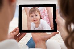 Couple looking at image of baby. Couple Looking At Tablet Screen With The Image Of Baby Royalty Free Stock Photography