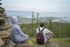 Couple looking at lake Baikal from top of the hillock dedicated to a local Tutelary deity. Siberia, Russia stock images
