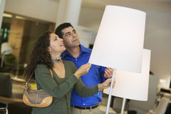 Couple Looking At Lamps In Furniture Store Royalty Free Stock Photography