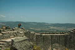 Couple looking the landscape from wall at the Castle of Monsanto. Couple looking the countryside landscape from the stone wall on rocky hill, in a sunny day at stock photos