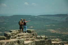 Couple looking the landscape from wall of Castle. Monsanto, Portugal - July 13, 2018. Couple looking the countryside landscape from stone wall at the Castle of stock photo