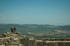 Couple looking the landscape from wall of Castle. Monsanto, Portugal - July 13, 2018. Couple looking the countryside landscape from stone wall at the Castle of royalty free stock photo