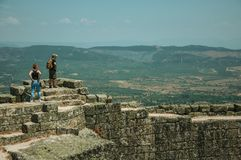 Couple looking the landscape from wall of Castle. Monsanto, Portugal - July 13, 2018. Couple looking the countryside landscape from stone wall at the Castle of stock images