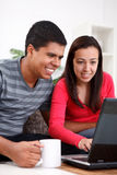 Couple Looking at Laptop. Young couple  looking at a laptop together in their living room Stock Photography