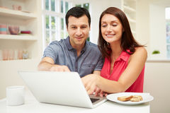 Couple Looking at Laptop Over Breakfast Stock Photography