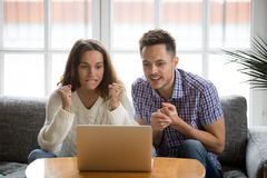 Couple looking at laptop screen supporting team watching match. Nervous excited couple in tension clenching fists looking at laptop screen, men and women Royalty Free Stock Photography