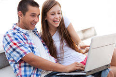 Couple looking at laptop together. Portrait of young couple outdoors Royalty Free Stock Images