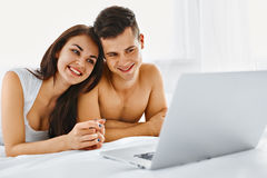 Couple looking at laptop. Young beautiful couple looking at laptop while lying on the bed in their bedroom. Communication technology Royalty Free Stock Photography