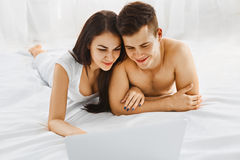 Couple looking at laptop. Young beautiful couple looking at laptop while lying on the bed in their bedroom. Communication technology Stock Photo